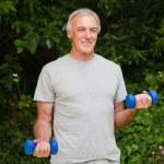 Senior man doing his exercises in the garden — Stock Photo #10848531