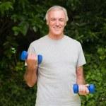Senior man doing his exercises in the garden — Stock Photo #10848535