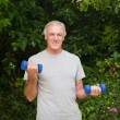 Senior man doing his exercises in the garden — Stock Photo