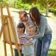 Family painting together in the park — Stock Photo