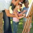 Family painting together in the park - Stock Photo