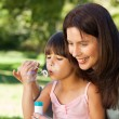 Girl blowing bubbles with her mother in the park - Stockfoto