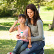 Girl blowing bubbles with her mother in the park - Stok fotoraf