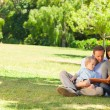 Family looking at their photo album in the park — Foto Stock