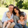 Family sitting in the park — Stock Photo #10849269