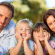 Family lying down in the park — Stock Photo #10849429