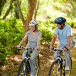 Elderly couple mountain biking outside - Foto Stock
