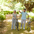Couple with their bikes in the wood - Stock Photo