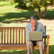 Elderly man working on his laptop in the park — Stock Photo #10849949