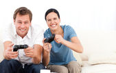 Excited woman playing video games with her boyfriend on the sofa — 图库照片