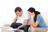 Worried couple looking at their bills on the sofa — Stock Photo