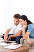 Desperate couple doing their account sitting on the sofa — Stock Photo