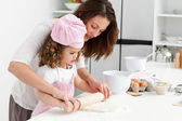Mother and daughter using a rolling pin together — Stock Photo