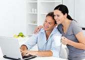 Affectionate woman looking at her boyfriend working on the lapto — Stock Photo