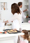 Cute little girl taking cookies while her parents are cooking — Stock Photo