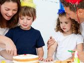 Madre e hijo cortando un cumpleaños pastel juntos — Foto de Stock