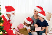 Santa giving presents to his children in the living room — Stock Photo