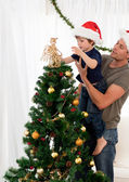Cute son decorating the christmas tree with his father — Stok fotoğraf