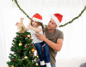 Cute daughter decorating the christmas tree with his father — Stok fotoğraf