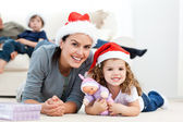 Happy mother and daugher at christmas lying on the floor — Stock Photo