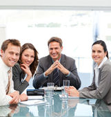 Portrait of a positive manager with his team sitting at a table — Stock Photo
