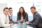 Portrait of a businesswoman with her team sitting at a table — Stock Photo