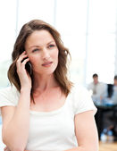 Pensive businesswoman on the phone while her team is working — Stock Photo