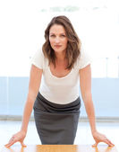 Confident businesswoman posing leaning on a table — Foto de Stock
