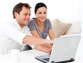 Cute man showing something on the laptop screen to his girlfrien — Stock Photo