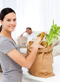 Happy woman with bags in the kitchen after shopping — Stock Photo