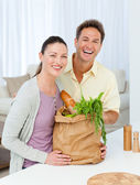 Couple laughing standing in the kitchen with shopping bags — Stock Photo