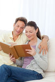 Cute couple looking at a photo album on the sofa — Stock Photo