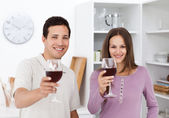 Young couple toasting with glasses of red wine — Stock Photo
