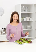 Cute woman mixing a salad standing in the kitchen — Foto Stock