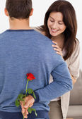 Impatiente woman looking at a flower hidden by her boyfriend — Stock Photo