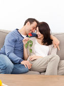 Enamored couple sitting together on the sofa — 图库照片