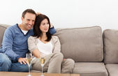 Relaxed couple watching television while drinking champagne — Stock Photo