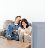 Miedo par ocultando sus rostros mientras ve una película de terror — Foto de Stock