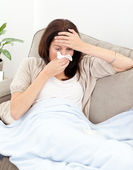 Tired woman feeling her temperature while blowing her nose — Stock Photo