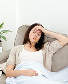 Sick woman taking her temperature with a thermometer on the sofa — Stock Photo
