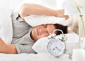Frustrerad man lyssnar på hans väckarklocka — Stockfoto