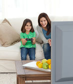 Pretty mom encouraging her daughter playing video games — Stock Photo