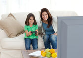 Mom and daughter playing video games together — Stock Photo