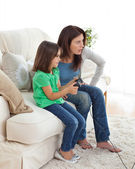 Concentrated mom and daughter playing video games — Stock Photo