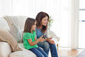 Attentive mother encouraging her daughter playing video games — Stockfoto
