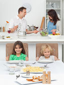 Brother and sister playing with forks while their parents cookin — Stock Photo