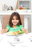 Adorable llittle girl holding forks to eat pasta and salad — Stock Photo
