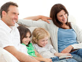 Parents and children watching television together — Stock Photo