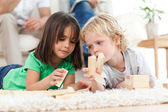 Little boy and girl playing with dominoes together — Stock Photo
