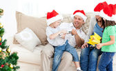Father and son playing with a cracker on the sofa — Stock Photo
